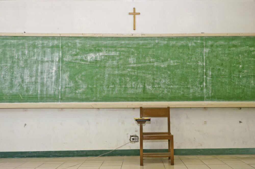10855179 - empty school blackboard in classroom with crucifix and chair