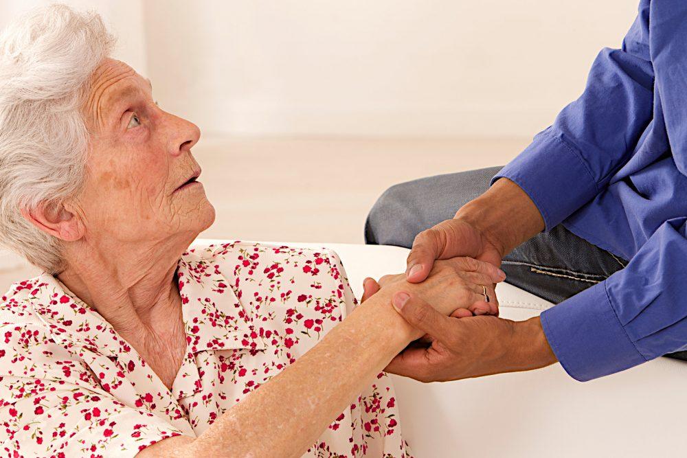 Caregiver holding elderly lady's hands.