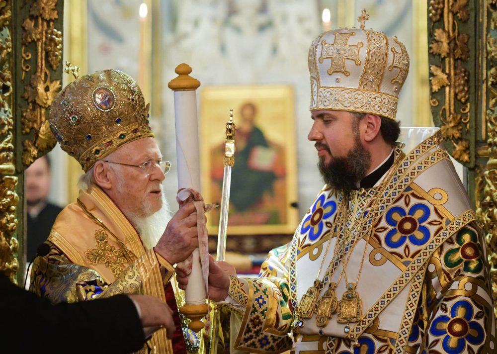 Ecumenical Patriarch Bartholomew I, left, presents the