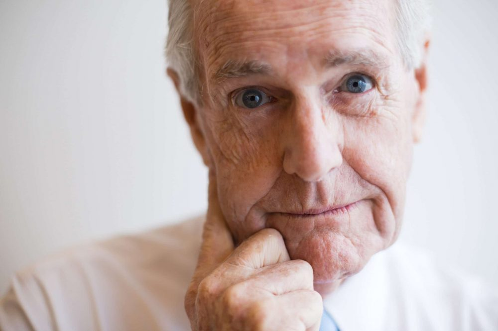 Close-up of pensive face of senior businessman staring at camera with hand on chin