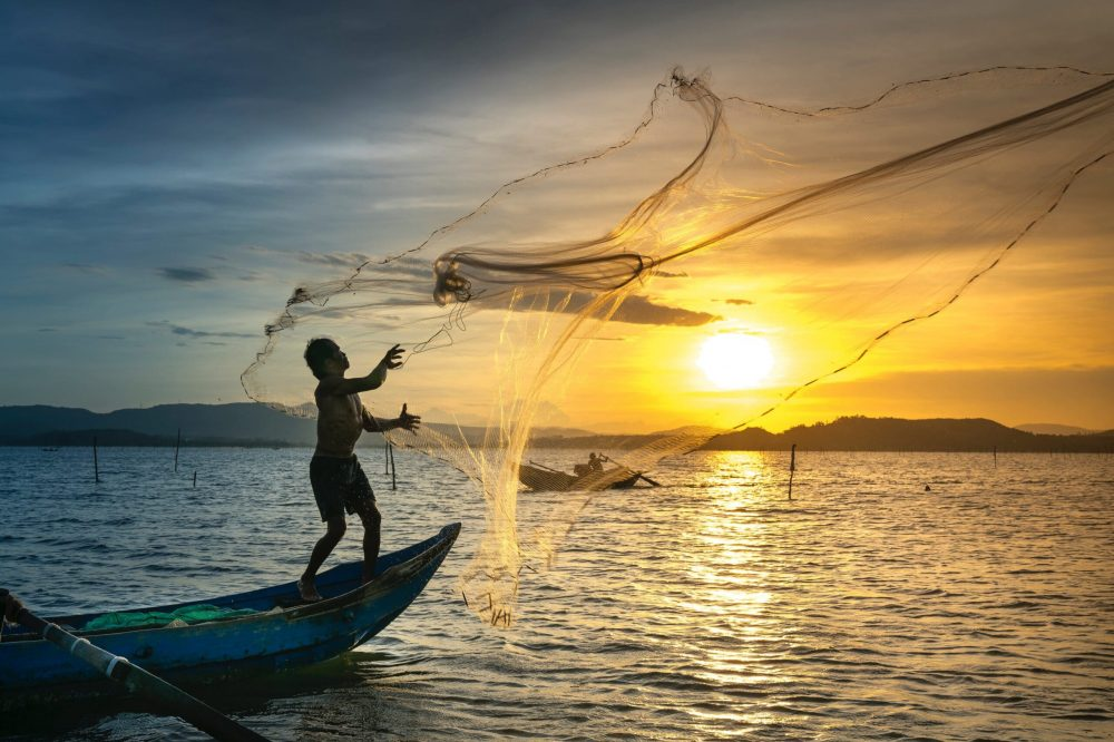 person-throwing-fish-net-while-standing-on-boat-2131967