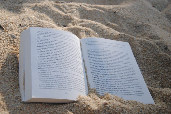 white-book-on-sand-during-daytime-159597